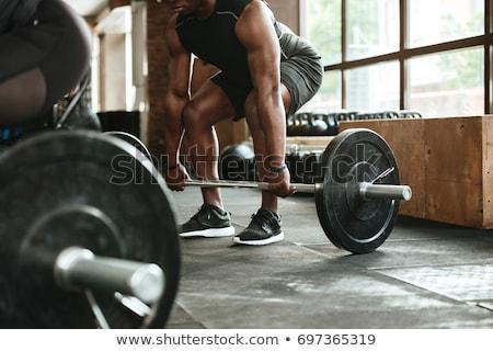 Muscular strong sportsman lifting barbell Stock photo © deandrobot