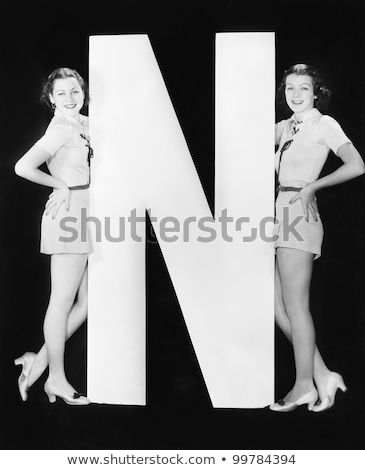 Vertical image of two smiling women posing in studio stock photo © deandrobot