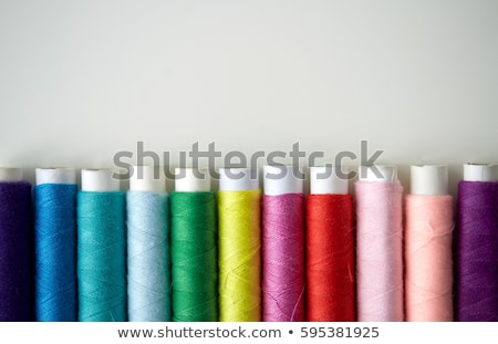 row of colorful thread spools on table stock photo © dolgachov