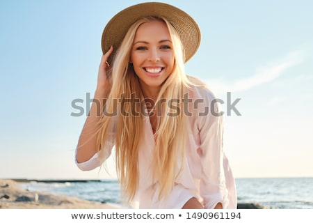 Beautiful young blonde girl in hat on the beach stock photo © Massonforstock