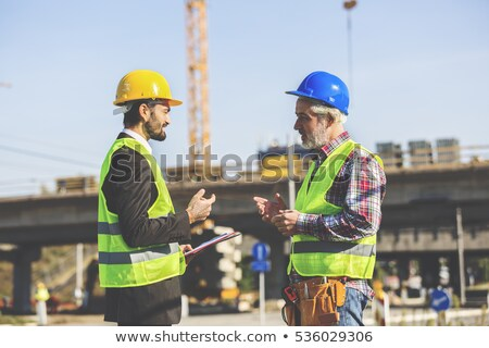 Businessman and worker talking on site Stock photo © IS2