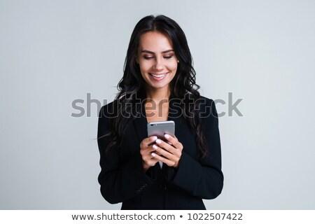 üzletasszony · mobiltelefon · fiatal · ül · iroda · mosolyog - stock fotó © wavebreak_media