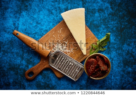 grated parmesan cheese and metal classic grater placed on wooden cutting board stock photo © dash