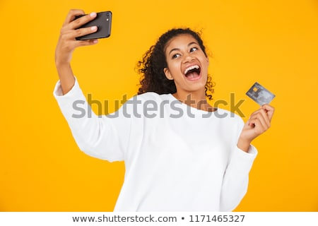 african woman posing isolated over yellow background take a selfie by mobile phone stock photo © deandrobot