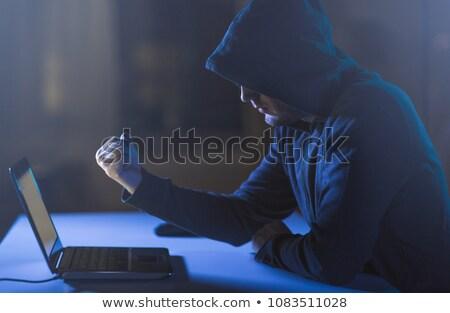 Hacker mutat ököl laptop sötét szoba Stock fotó © dolgachov