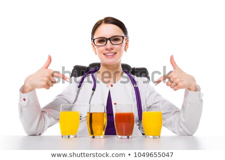 Female nutritionist sitting in her working place showing and offering glass of pineapple fresh juice Stock photo © Traimak