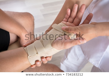 orthopedist fixing plaster on injured womans hand stock photo © andreypopov