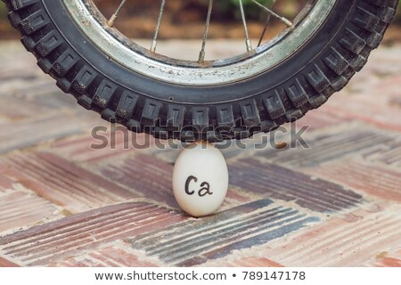 Egg - calcium, under the heavy wheel of a bicycle does not break. The power of the calculus concept Stock photo © galitskaya