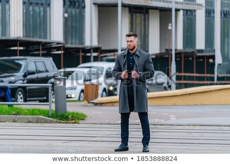 attractive man smiling and walking on the side of the road Stock photo © feedough