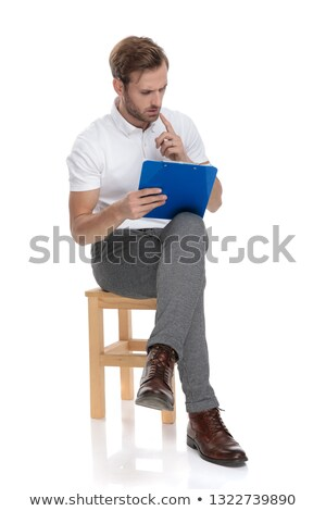 man sitting and solving a difficul problem on his clipboard, Stock photo © feedough