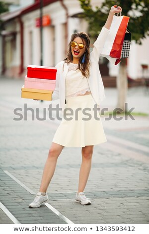 Happy model in white look and sunglasses holding shopping bags u Stock photo © studiolucky