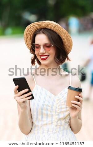 Tevreden brunette vrouw strohoed zonnebril smartphone Stockfoto © deandrobot