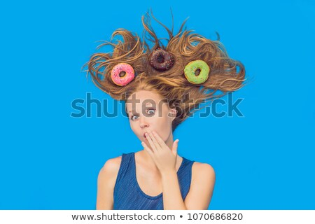 Young woman with donuts in her hair. Multicolored donuts. Harm of sweet Stock photo © galitskaya