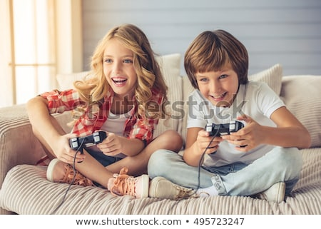 brother and sister play video game on sofa Stockfoto © Lopolo