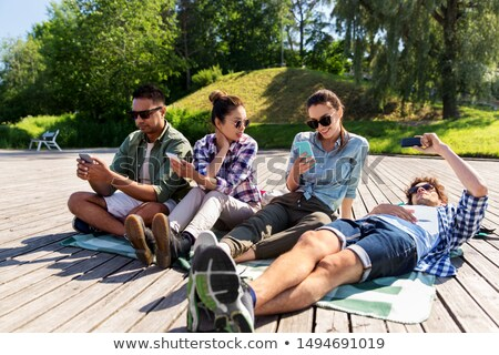 friends with smartphones chilling at summer park Stock photo © dolgachov