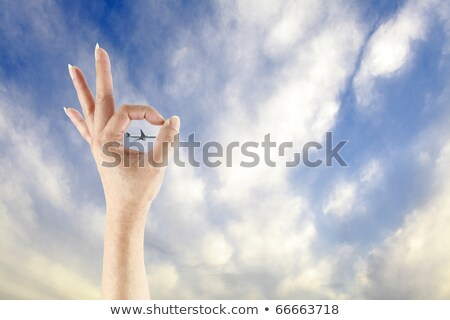 A hand showing the okay symbol with an airplane flying through the finger against a clear blue sky. Stock photo © Lopolo