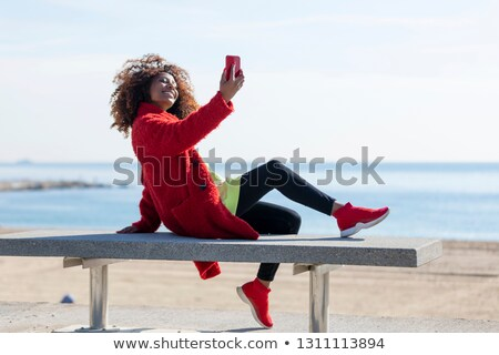 Side View Of Young Woman Taking Selfie With Mobile Phone At Beach Stockfoto © 2Design