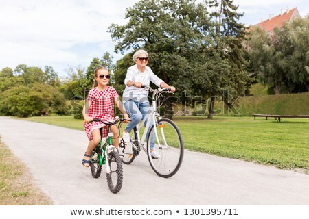 grandmother and granddaughter cycling at park Stock photo © dolgachov
