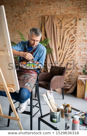 Contemporary painter in casualwear and apron mixing colors on palette Stock photo © pressmaster