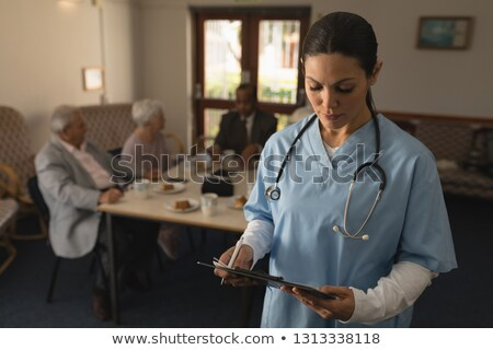 front view of young female doctor looking at clipboard with her patient behind her at nursing home stock photo © wavebreak_media