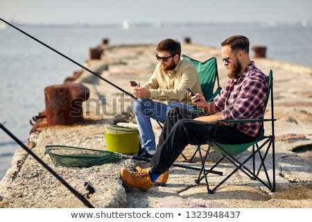 friends with smartphones fishing on pier at sea Stock photo © dolgachov