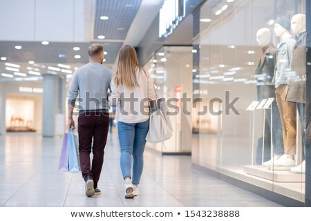 Rear view of young casual couple moving along shop window in the mall Stock photo © pressmaster