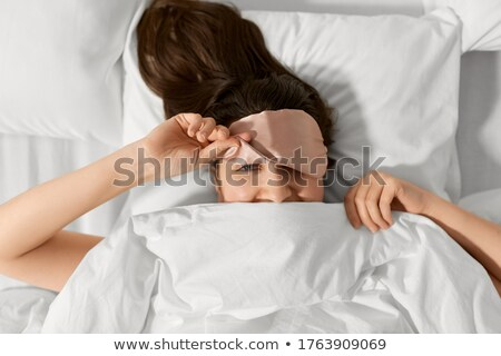 happy young woman peeking from under sleeping mask Stock photo © dolgachov