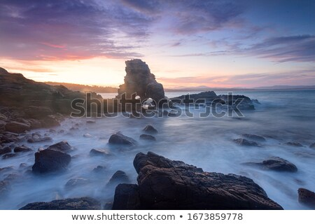 Sun setting behind the cave arch rock Stock photo © lovleah