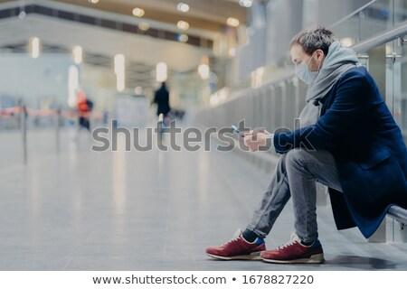 Sideways shot of man tourist returned from abroad, wears medical Stock photo © vkstudio