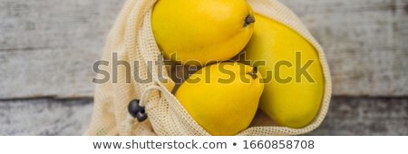 Mango in a reusable bag on a stylish wooden kitchen surface. Zero waste concept, plastic free concep Stock photo © galitskaya