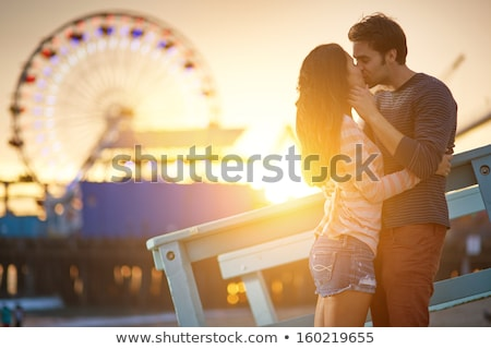 couple kissing in the park at sunset stock photo © massonforstock