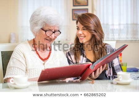 two senior friends looking at a photo album Stock photo © photography33