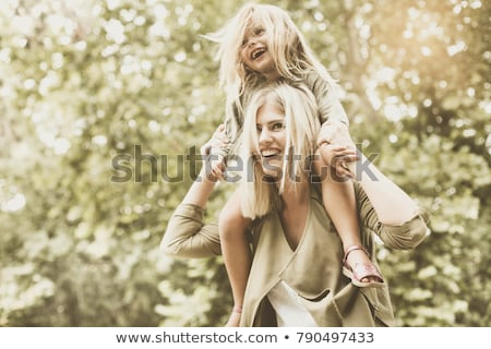 Foto d'archivio: Young Child Riding On Her Mothers Shoulders