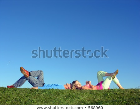 Stock photo: couple lie on blue sky girl look at you