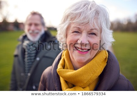 Smiling woman looking at camera in winter park Stock photo © deandrobot