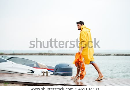Sailor in yellow cloak at the pier holding life vest Stock photo © deandrobot
