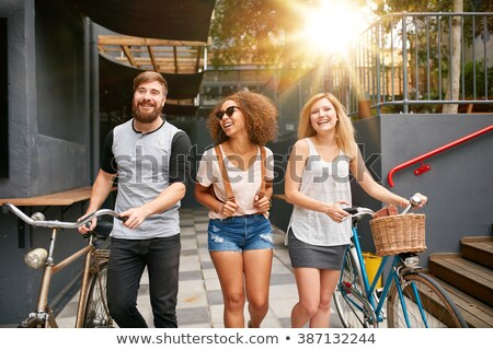 Young brunette woman riding on bicycle in city street Stock photo © deandrobot