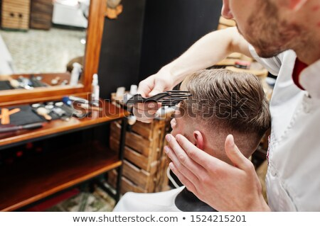 Handsome young man getting beard haircut while sitting in chair Stock photo © deandrobot