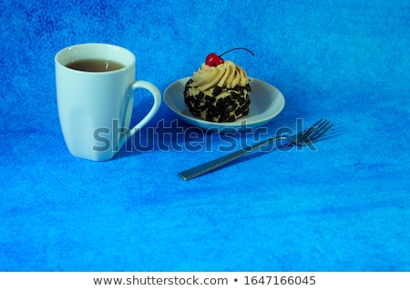 Cake with fresh berries on a blue plate next to a cup of tea and Stock photo © d_duda