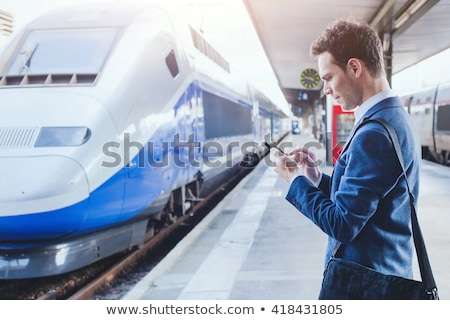 business man using smartphone at train station stock photo © szefei