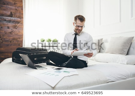 Businessman on bed working with a tablet and laptop from his hotel room Stock photo © tommyandone