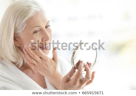 senior woman applying face cream stock photo © lightfieldstudios