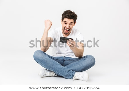Excited young man make winner gesture. Stock photo © deandrobot