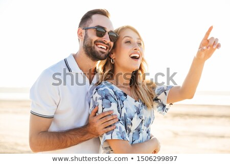 Image of two lovely girls smiling and pointing fingers upward to Stock photo © deandrobot