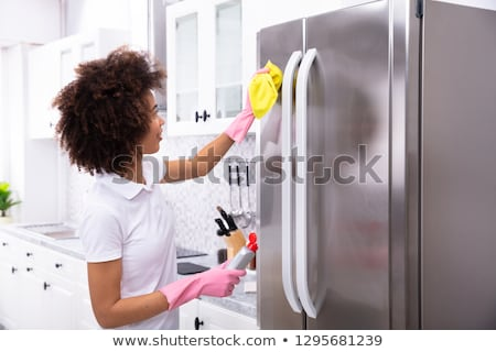 Stockfoto: Jonge · vrouw · schoonmaken · koelkast · servet · ernstig