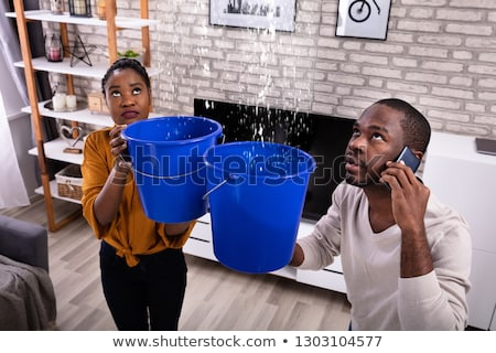 Couple Using Bucket For Collecting Water Leakage From Ceiling Stock photo © AndreyPopov