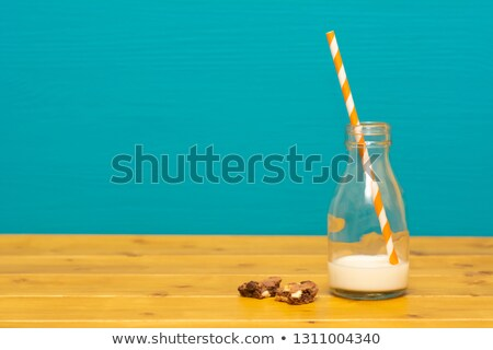 Straw and bottle half full of milk, and cookie crumbs Stock photo © sarahdoow