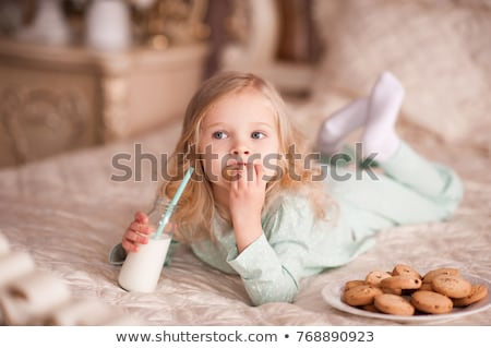 Little girl in pajamas holding glass of milk Stock photo © colematt