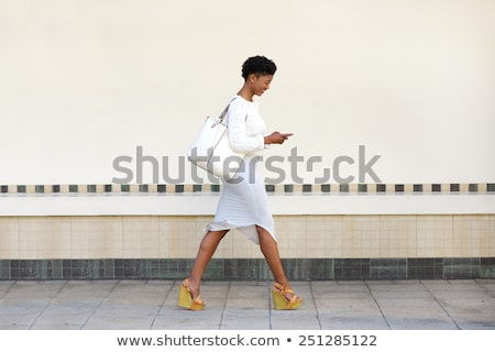 african young woman walking outdoors using mobile phone stock photo © deandrobot