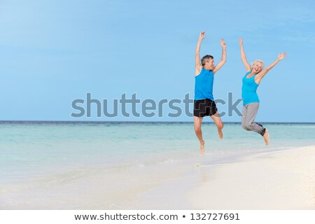 happy couple in sports clothes jumping on beach stock photo © dolgachov